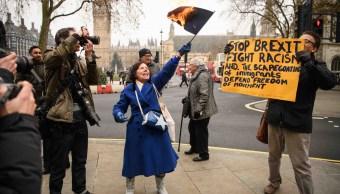 Mujer quema bandera de la Unión Europea (centro), hombre en contra de Brexit sostiene pancarta (derecha).