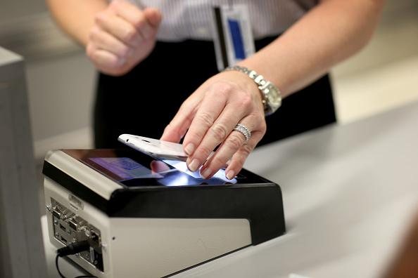 Un elemento de la Oficina de Aduanas y Protección Fronteriza de los Estados Unidos escanea un teléfono en la zona de arribos en el aeropuerto de Miami, EU. (Getty Images, archivo)