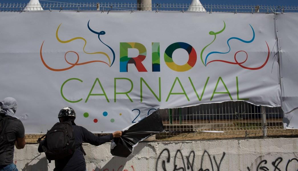 Un manifestante arranca una pancarta de Carnaval de Río junto al Sambódromo durante una protesta contra el gobierno estatal en Río de Janeiro, Brasil (AP)