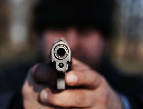 Una persona apunta con una pistola; en la Ciudad de México, personal de la PGR detienen a un individuo por portar un arma de fuego de manera ilegal