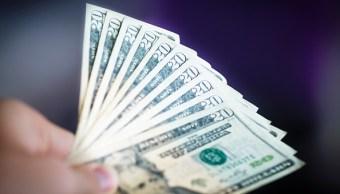 Foto ilustrativa de un hombre sosteniendo varios billetes americanos (Getty Images)