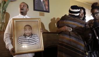 Familiares sostienen un retrato de Ezell Ford, un joven muerto a tiros por la policía de Los Ángeles.