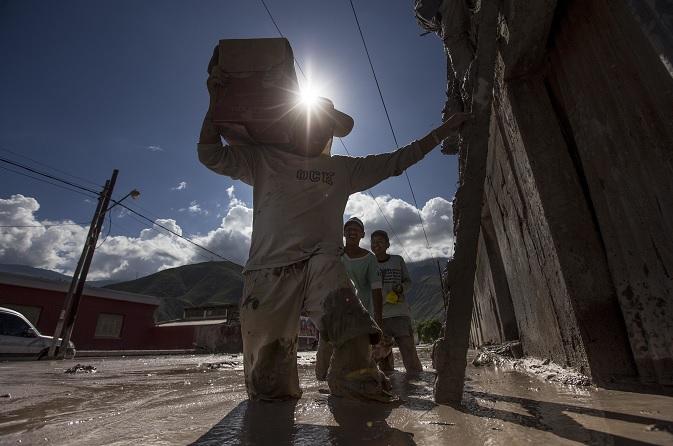 Residentes de la provincia de Jujuy, en Argentina, llevan su pertenencia a los techos de sus casas inundadas (AP)