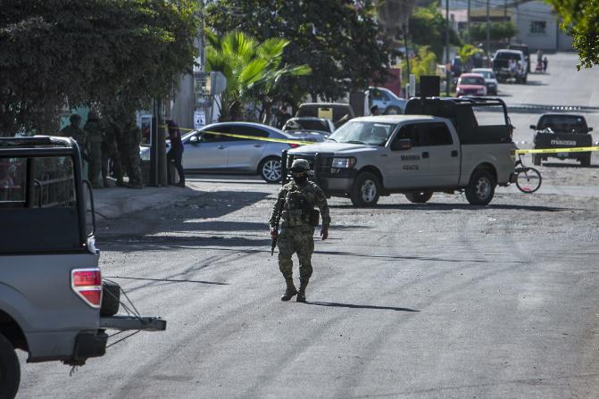 Un marino camina en una calle cercana donde se registró un enfrentamiento en Culiacán, Sinaloa (AP)