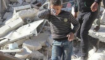 Un joven camina sobre los escombros de un edificio derrumbado tras ataques aéreos en Alepo, Siria (Getty Images/archivo)