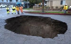 Un grupo de bomberos examinan un socavón al norte de Los Ángeles. Al menos dos vehículos cayeron en su interior (AP)