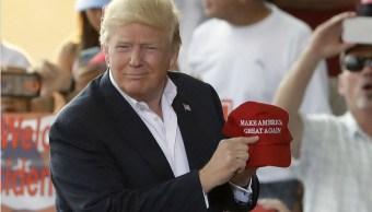 """El presidente Donald Trump apunta a su lema en una gorra, durante el """"Make America Great Again Rally"""" en el Aeropuerto Internacional de Orlando-Melbourne, este sábado. (AP)"""