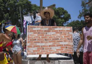 Un joven brasileño sujeta una tela simulando un ladrillo, en alusión al muro que Trump pretende construir en la frontera con México. (AP)