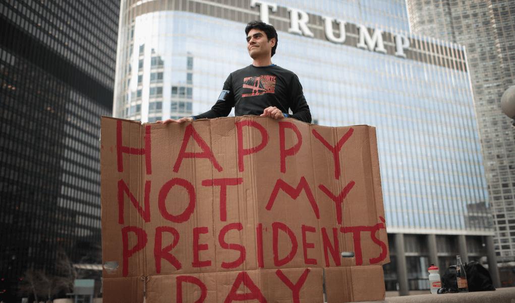 Un manifestante sostiene un cartel asegurando que Donald Trump no es su presidente.