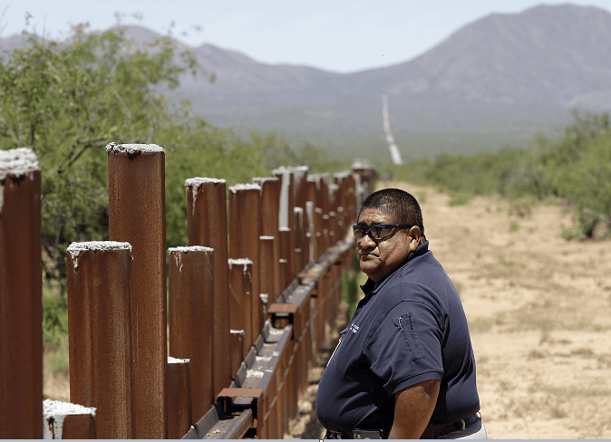 Un sargento de la policía de la etnia tohono o'odham camina junto a la valla fronteriza entre EU y México, en la zona de Arizona. (AP, archivo)