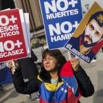 Mujer sostiene carteles con imagen de Leopoldo Lopez