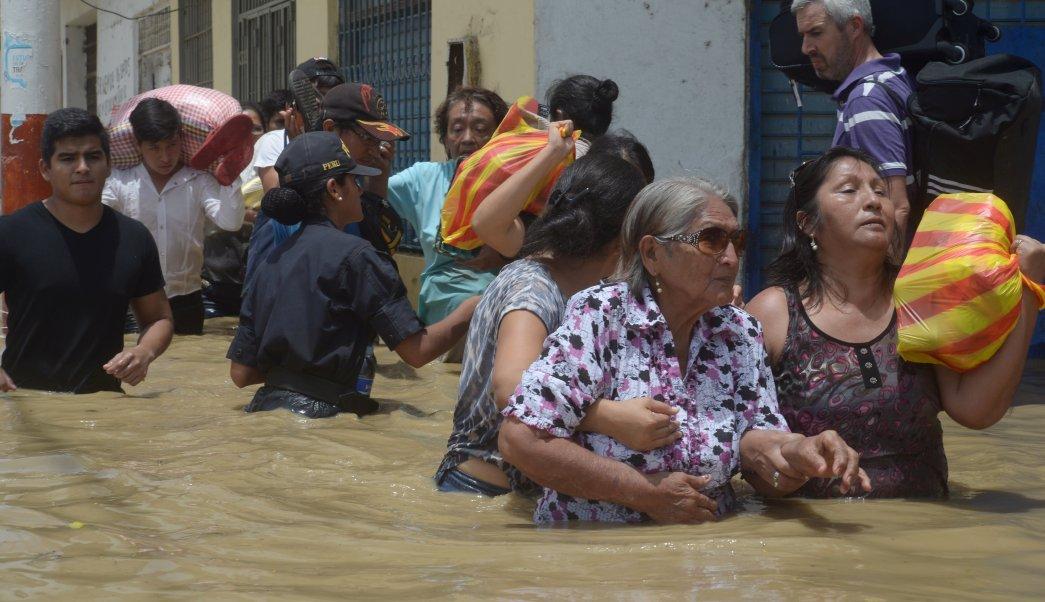 Residentes cruzan una calle inundada después del desbordamiento de ríos por las lluvias torrenciales en Piura, Perú. (Reuters)