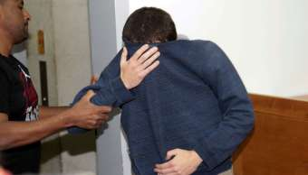 El joven cubre su rostro mientras es llevado a la corte en Rishon Lezion, Israel, por ser el principal sospechoso de realizar amenazas de bomba a instituciones judías. (AP)