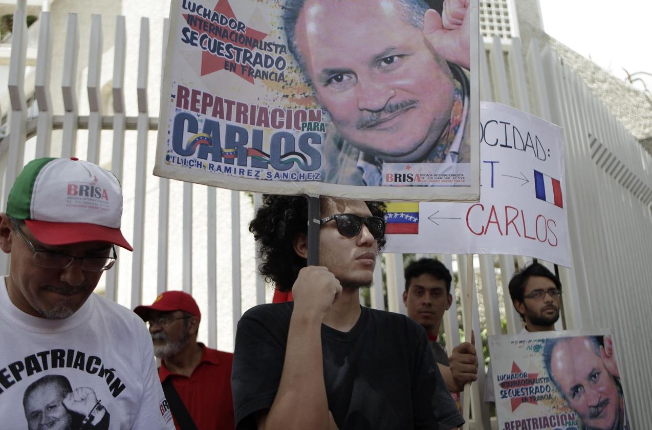 """Un grupo de manifestantes tienen carteles del venezolano Ilich Ramírez Sánchez, más conocido como Carlos """"El Chacal"""", frente a la embajada de Francia, exigen su regreso a Venezuela (AP)"""