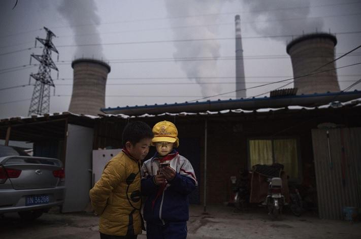 Niños chinos miran su smartphone delante de su casa al lado de una central eléctrica (Getty Images)
