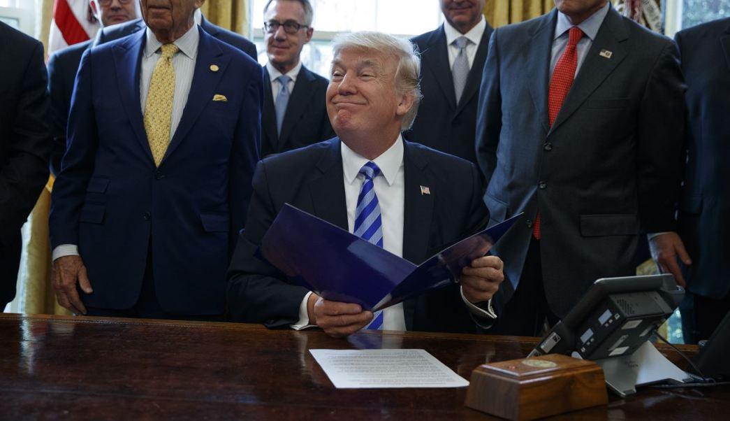 El presidente Donald Trump, acompañado por el secretario de Comercio, Wilbur Ross, y el secretario de Energía, Rick Perry, en la Oficina Oval de la Casa Blanca en Washington. (AP)