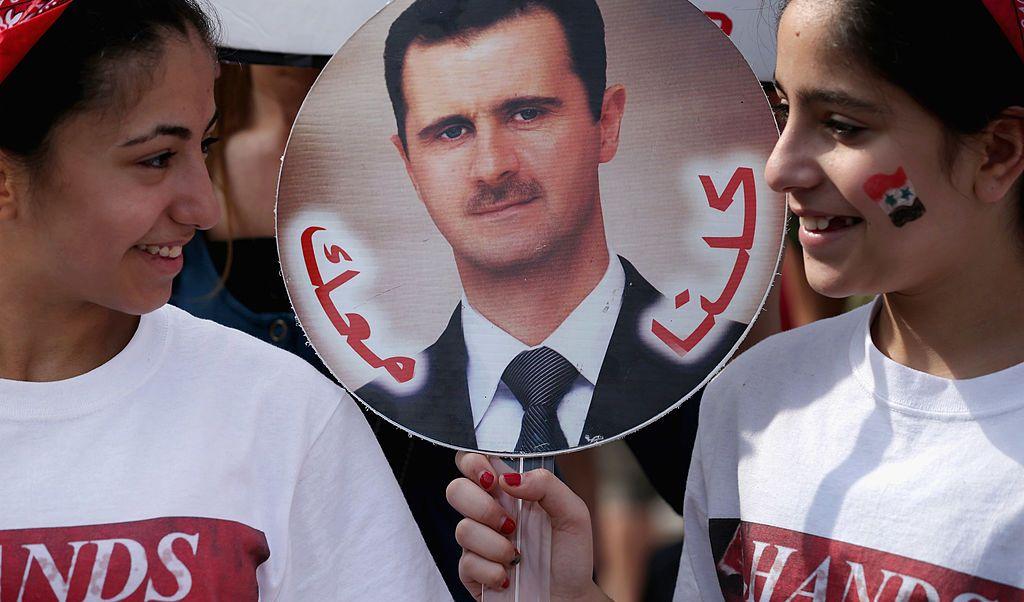 Dos niñas sostienen un cartel con la imagen del presidente sirio Bashar al Assad.