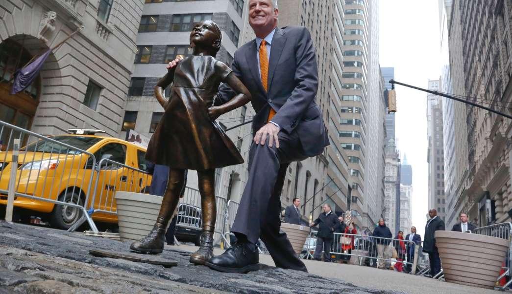 El alcalde de Nueva York, Bill de Blasio, posa junto a la escultura de la 'Niña sin Miedo' en Wall Street (AP)