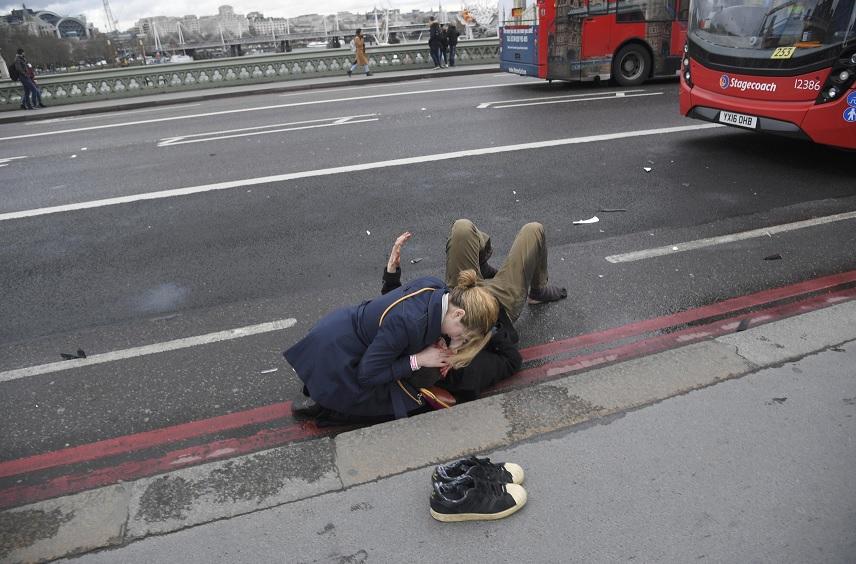 Una mujer ayuda a una persona herida después de un incidente en el puente de Westminster en Londres (Reuters)