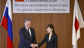 """El ministro ruso de Defensa, Sergei Shoigu, estrecha la mano con su homóloga japonesa, Tomomi Inada; se trata de la primera reunión """"Dos más dos"""" que Rusia se anexó Crimea. (AP)"""