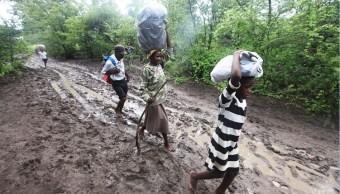 Pobladores de Tsholostho transportan alimento; la región sur de Zimbabue es golpeada por fuertes lluvias e inundaciones (AP)