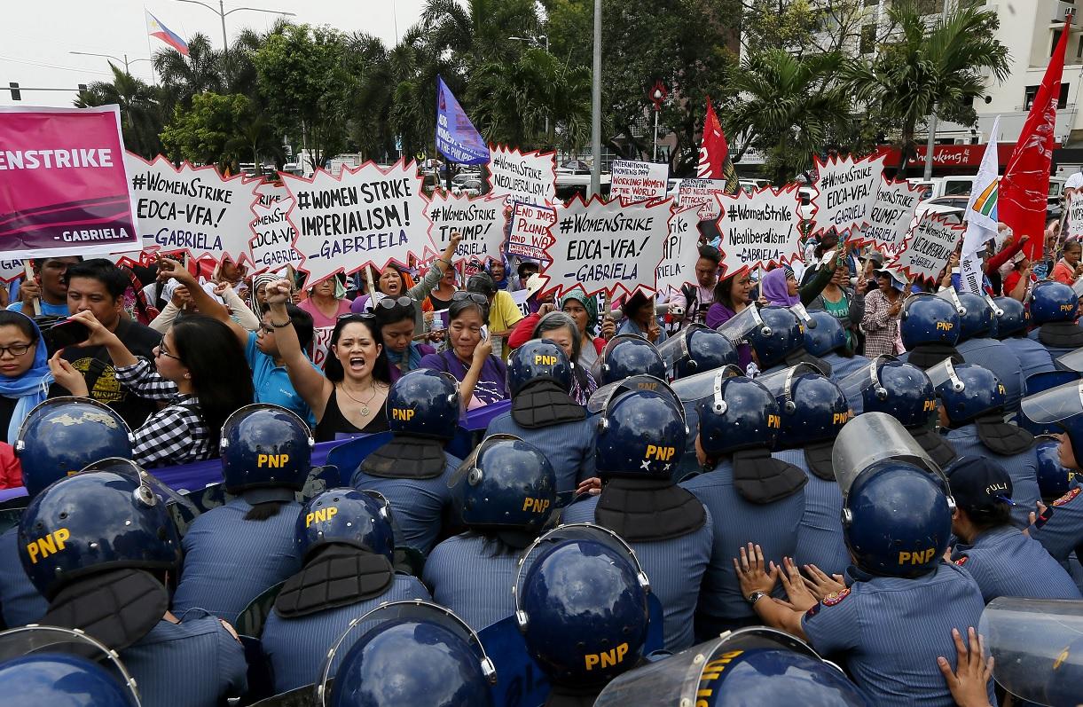 La policía bloquea a manifestantes durante un mitin en la Embajada de los Estados Unidos para celebrar el Día Internacional de la Mujer (AP)