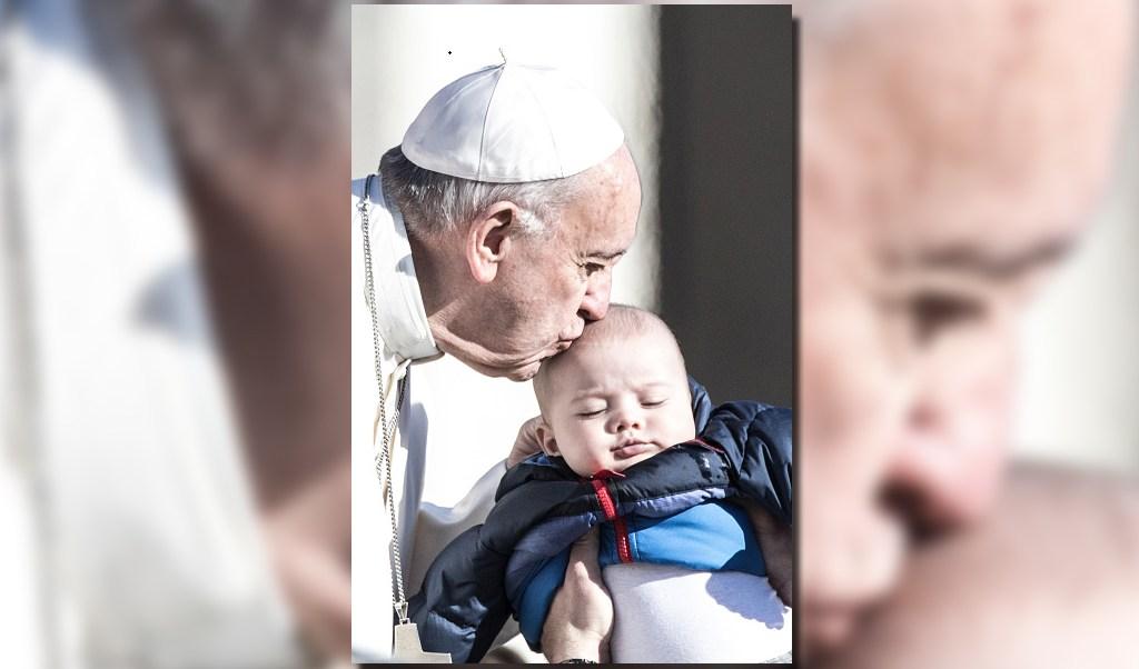 El papa Francisco besa a un bebé luego de la audiencia general de los miércoles. (AP)