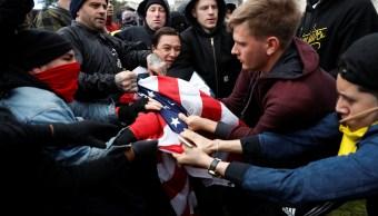 Seguidores y detractores de Donald Trump se enfrentan y pelean por una bandera de Estados Unidos en Berkeley, California (Reuters)