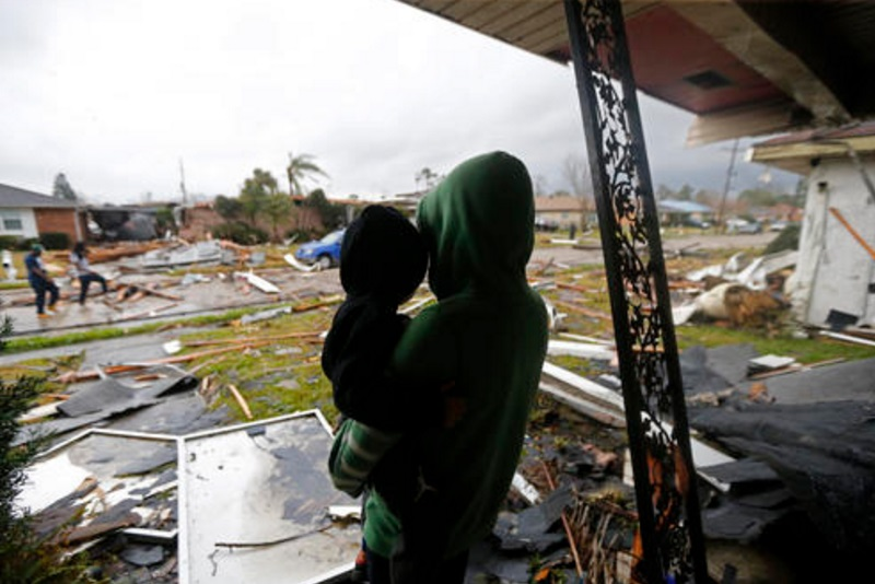 Eshon Trosclair sostiene a su hijo tras severas tormentas en el este de New Orleans, Estados Unidos (AP)