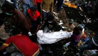 Trabajadores de rescate llevan el cuerpo de una víctima recuperada de un montón de basura después de un deslizamiento de tierra en la capital de Etiopía (Reuters)