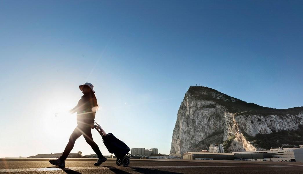 Una mujer camina por el lado español de la frontera entre España y el territorio británico de ultramar de Gibraltar con la roca como telón de fondo. (AP)