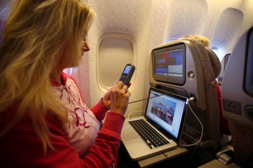 Una mujer trabaja con una computadora portátil y hace una llamada telefónica a bordo de un avión de pasajeros Emirates Airline en Trivandrum, India (Getty Images)