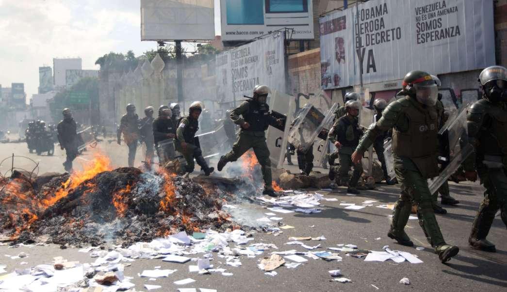 Los funcionarios de la Guardia Nacional Bolivariana se desplazan sobre una barricada en llamas durante una protesta en Caracas, Venezuela. (AP)