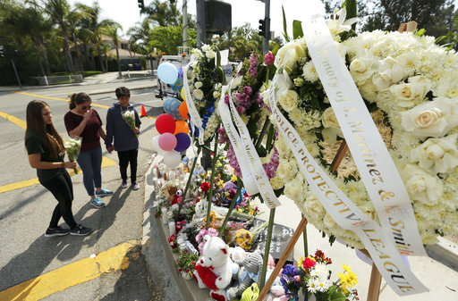 Algunas personas acudieron este martes para rezar y colocar flores en un memorial montado sobre la banqueta fuera de la escuela de San Bernardino, EU. (AP)