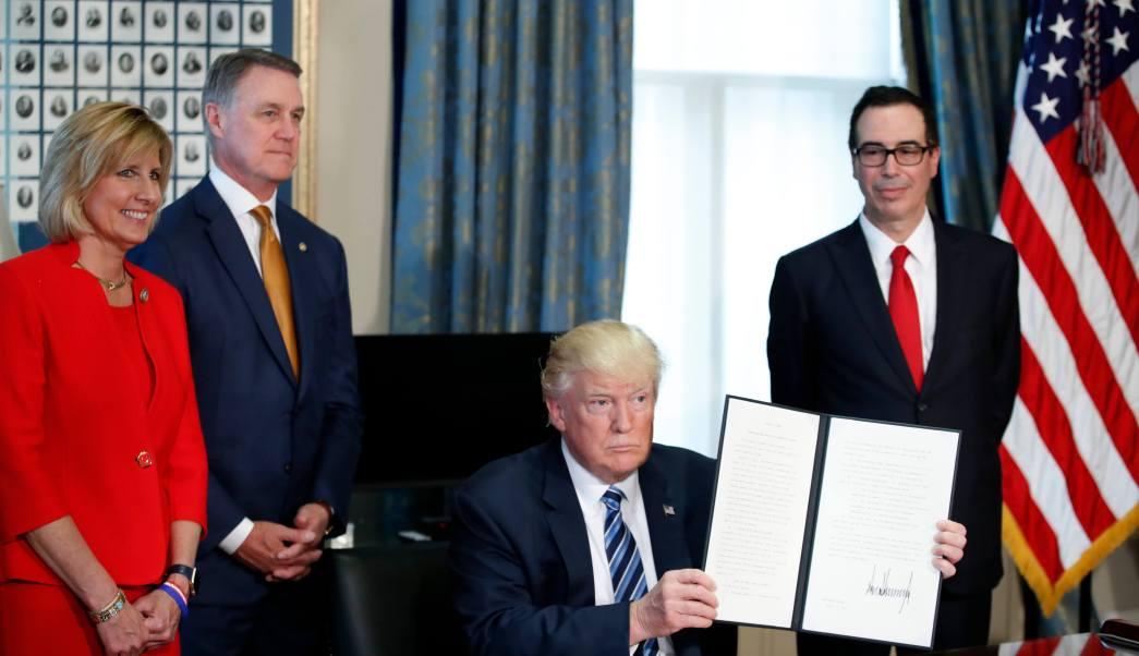 El presidente de Estados Unidos, Donald Trump, acompañado por la congesista Claudia Tenney, el senador David Perdue, y el secretario del Tesoro Steve Mnuchin tras firmar una orden ejecutiva. (AP)