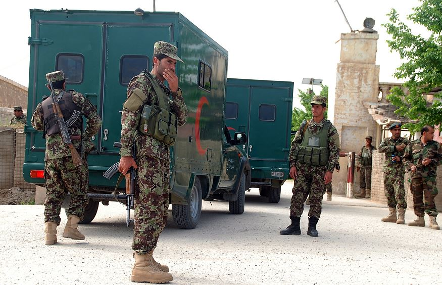 Militares afganos hacen guardia mientras las ambulancias entran a la base militar, lugar del ataque talibán. (AP)