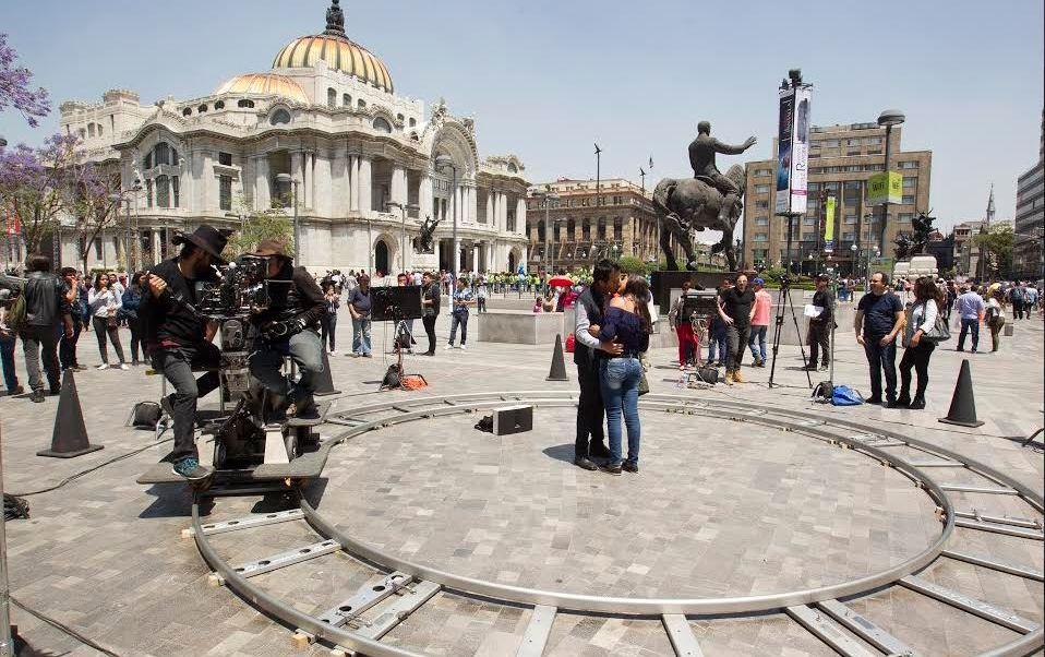 Decenas de parejas participan en la obra 'Besos Públicos', en la explanada del Palacio de Bellas Artes, en la Ciudad de México; se trata de una iniciativa del artista mexicano Carlos Santos, en la que invita a los voluntarios a compartir lo íntimo en público. (Twitter@danetteCass)