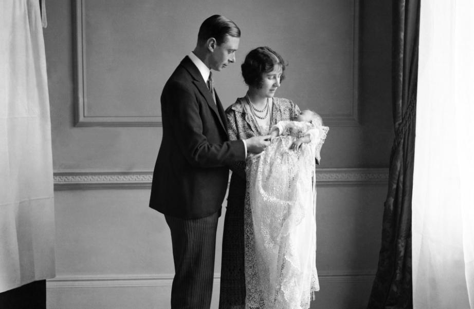 Fotografía de la reina Isabel II durante su bautizo en 1926, acompañada por sus padres. (@RoyalFamily)