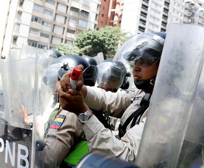 Las fuerzas de seguridad bloquean una calle con escudos antidisturbios y utilizan gas pimienta durante un mitin de la oposición en Caracas, Venezuela (Reuters)
