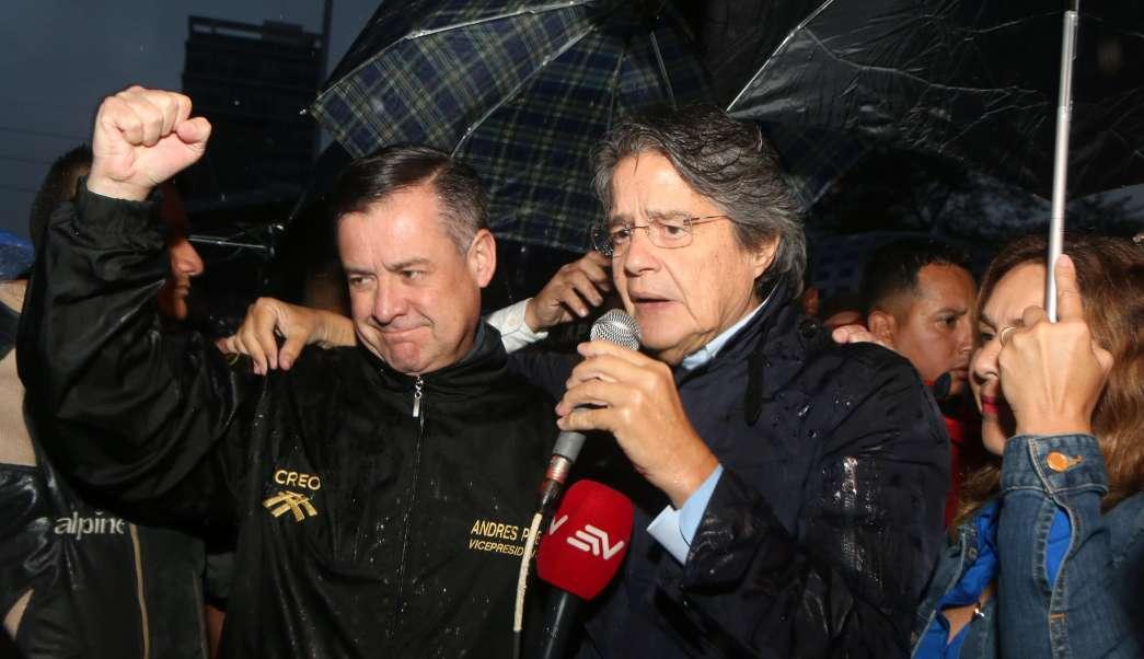 El candidato presidencial ecuatoriano Guillermo Lasso (c), acompañado de su fórmula vicepresidencial Andrés Paez (i), y su esposa María de Lourdes Alcivar (d), habla ante sus simpatizantes; el movimiento opositor de Ecuador Creando Oportunidades (CREO) impugnó formalmente los resultados de las elecciones presidenciales del 2 de abril (EFE)