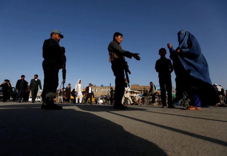 Una familia afgana espera a que los policías desbloqueen el camino cerca del sitio de un atentado suicida en Kabul, Afganistán (Reuters)