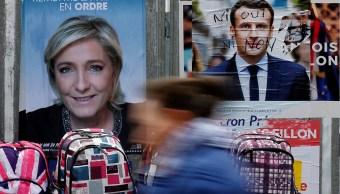 Carteles de Emmanuel Macron y Marine Le Pen, quienes disputarán la segunda vuelta presidencial (Reuters, archivo)
