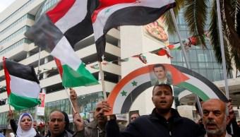 Un grupo de palestinos tienen un cartel del presidente Bashar al-Assad, durante una protesta contra los ataques aéreos estadounidenses en Siria (Reuters)