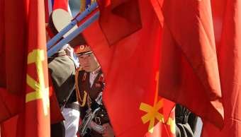 soldado norcoreano se asoma detras de varias banderas de su pais
