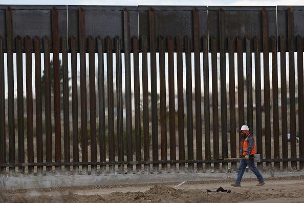 Un contratista camina por una sección construida de una valla fronteriza que separa a Estados Unidos y México en Sunland Park, Nuevo México (Getty Images/Archivo)