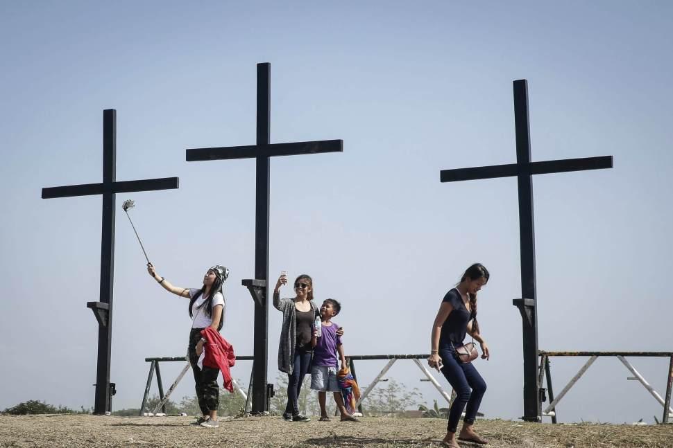 Turistas se hacen fotos junto a tres cruces tras la representación de la crucifixión de Cristo con motivo de la celebración del Viernes Santo en San Fernando, Filipinas (EFE)