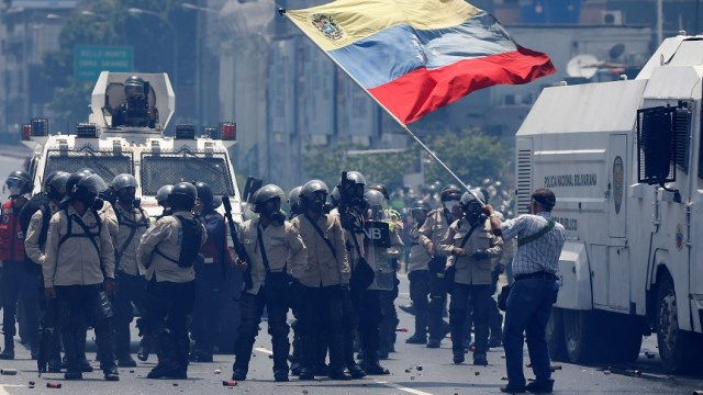 Un partidario de la oposición agita una bandera venezolana frente a la policía antidisturbios durante una manifestación contra el presidente de Venezuela, Nicolás Maduro (Reuters)