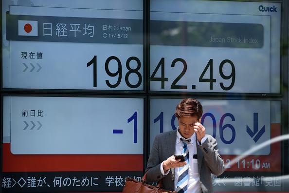 Peatón pasa frente a tablero electrónico de la Bolsa de Tokio