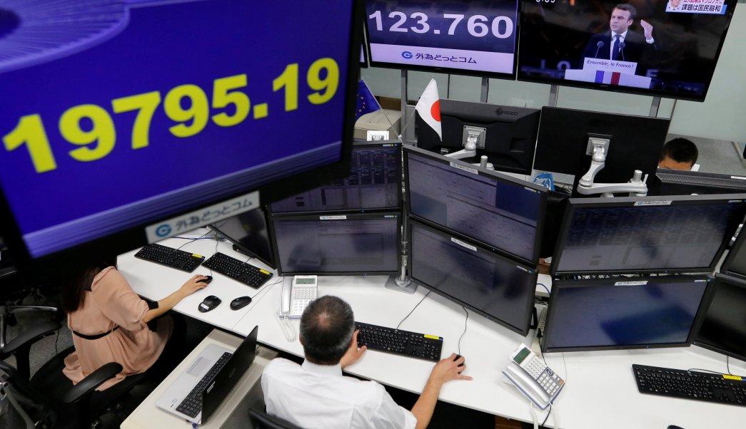 Empleados de casa de bolsa monitorean los índices financieros de japón