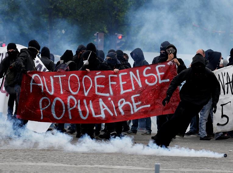 Manifestantes enmascarados se protegen de gases lacrimógenos en París (Reuters)